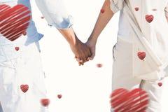 夫妇的综合图象在看对海的海滩的握手 免版税库存图片