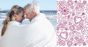 夫妇的综合图象坐海滩在微笑对彼此的毯子下 免版税库存照片
