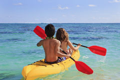夫妇皮船用浆划他们的年轻人 免版税库存照片