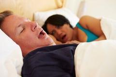 夫妇睡着在与打鼾的人的床上 免版税库存照片
