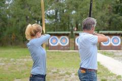 夫妇瞄准目标的射箭运动员 免版税库存图片