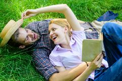 夫妇知己在浪漫日期 在爱的夫妇花费休闲阅读书 在草放松和女孩放置的人 图库摄影