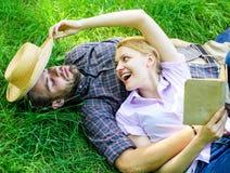 夫妇知己在浪漫日期 在草放松和女孩放置的人 在爱的夫妇花费休闲阅读书 库存图片