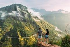 夫妇招呼在山的日出 男人和妇女山的 握手的男人和妇女 夫妇移动 免版税库存图片