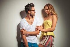 年轻夫妇穿戴的五颜六色获得乐趣,当看ea时 库存图片