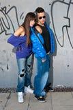 夫妇突出都市墙壁年轻人的方式纵向 免版税库存图片