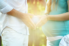 年轻夫妇等待婴孩由手指手做心脏 免版税库存照片