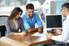 年轻夫妇签一辆新的汽车的购买的一个合同 免版税库存图片