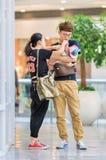 年轻夫妇繁忙与哺养的婴孩,北京,中国 图库摄影