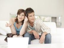 夫妇耳机回家共享沙发技术 免版税库存图片