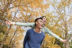 年轻夫妇肩扛在公园 库存照片