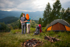 夫妇背包徒步旅行者在营火和帐篷附近站立  免版税库存照片