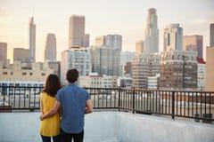 夫妇背面图在注视着在城市地平线的屋顶大阳台的日落 库存照片