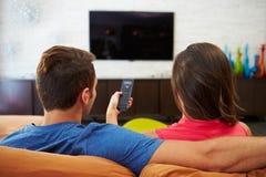 夫妇背面图坐一起看电视的沙发 库存照片
