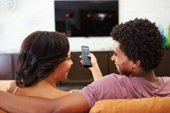 夫妇背面图坐一起看电视的沙发 免版税图库摄影