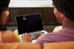 夫妇背面图坐沙发使用膝上型计算机 免版税库存图片