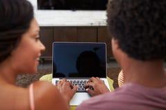夫妇背面图坐沙发使用膝上型计算机 图库摄影