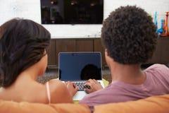 夫妇背面图坐沙发使用膝上型计算机 免版税图库摄影