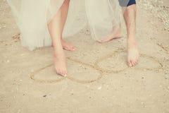 夫妇腿在沙子的油漆心脏 免版税库存照片
