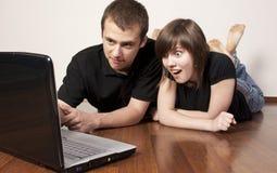 夫妇膝上型计算机使用 库存图片