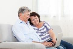 夫妇膝上型计算机前辈使用 库存图片