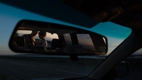 年轻夫妇自动镜子的反射,看看在日落的地图在路附近 免版税库存照片