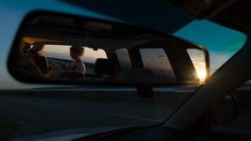 年轻夫妇自动镜子的反射,看看在日落的地图在路附近 库存图片