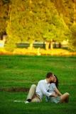 夫妇草坪公园坐的年轻人 库存图片