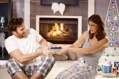 年轻夫妇获得乐趣在圣诞节早晨 免版税库存图片