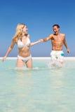 夫妇获得乐趣在海滩假日的海 免版税库存照片