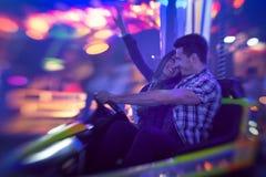 夫妇获得乐趣在碰撞用汽车 免版税图库摄影