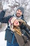 夫妇获得乐趣在积雪的公园 免版税库存照片