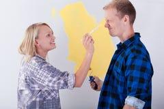 年轻夫妇获得乐趣在他们的新房 免版税库存图片