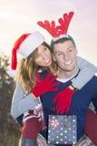 夫妇获得乐趣户外与圣诞节帽子 免版税库存照片