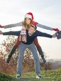 夫妇获得乐趣户外与圣诞节帽子 免版税库存图片