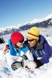 夫妇获得在滑雪节假日的乐趣在山 免版税图库摄影