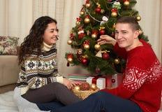 年轻夫妇装饰圣诞节杉树 与礼物的家内部 新年假日概念 爱和柔软 免版税库存图片