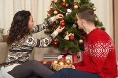 年轻夫妇装饰圣诞节杉树 与礼物的家内部 新年假日概念 爱和柔软 库存图片