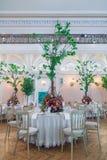 夫妇装饰玩偶玻璃被倒置的表婚礼 花美丽的花束在ta的 免版税库存图片
