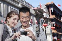 年轻夫妇观光,看数字照相机。 免版税库存图片