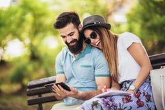 夫妇观看的媒介在室外一张数字的桌里 免版税库存照片