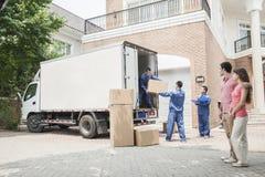 年轻夫妇观看的搬家工人从移动货车移动箱子 免版税图库摄影