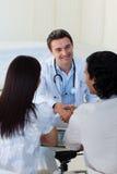 夫妇解释微笑的诊断医生 免版税库存照片
