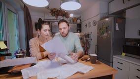 年轻夫妇计算的票据在厨房里在家 镇定哀伤和恼怒的丈夫的妇女尝试 股票录像