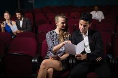 夫妇读书在剧院 免版税库存照片