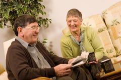 夫妇读高级妇女的人报纸 免版税库存图片