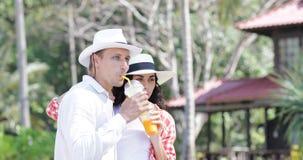 夫妇谈的饮料汁液在棕榈树、愉快的人和妇女旅游通信下热带假期 影视素材
