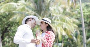 夫妇谈的饮料汁液在棕榈树、愉快的人和妇女旅游通信下热带假期 股票录像