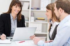 年轻夫妇谈话与妇女经纪 免版税库存图片