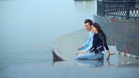 年轻夫妇谈话与微笑,当坐在河附近在堤防时